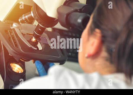 La imagen del científico mediante microscopio en laboratorio médico