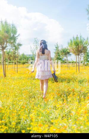 Vista trasera de una mujer hermosa en el vestido caminando por un campo de flores que llevan sus zapatos