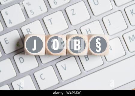 Cubos con la palabra 'JOB' y un símbolo de párrafo en un teclado