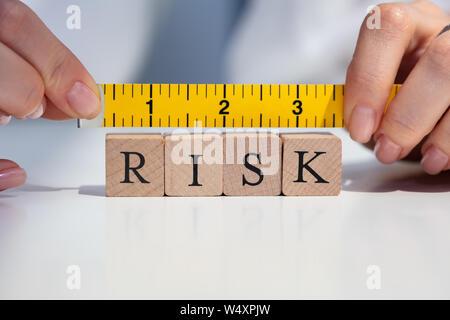 Close-up de una empresaria de la mano de medir el riesgo de bloques con la cinta de medición AMARILLA