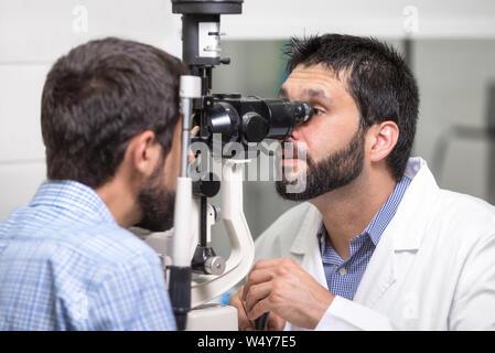 Macho médico oftalmólogo es controlar la visión del ojo del apuesto joven en la moderna Clínica. El médico y el paciente en oftalmología clínica .