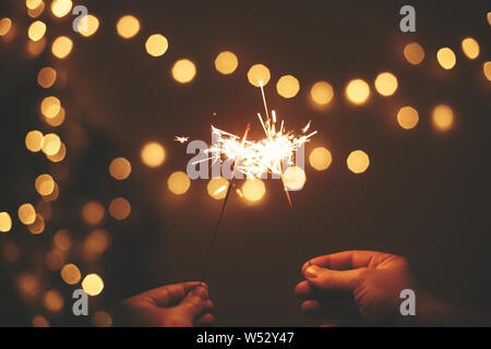 Feliz Año Nuevo. Brillantes estrellitas en manos sobre fondo de oro, un par de luces del árbol de Navidad La celebración festiva en la oscuridad de la habitación. Espacio para el texto. Fir