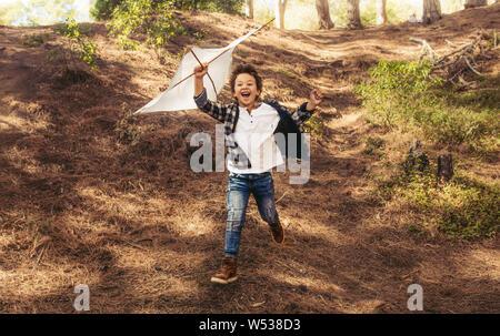 Muchacho feliz corriendo con un cometa en las manos por encima de su cabeza. Chico emocionado jugando con una cometa en el bosque. Foto de stock
