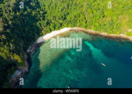 Antena drone vista de una playa pequeña en una exuberante isla tropical (Isla de la caverna)