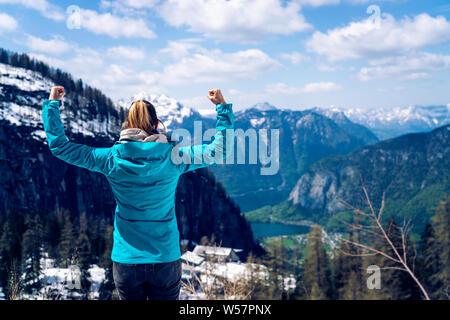 Hermosa muchacha en la cima de la montaña, mostrando un gesto ganador. Tema de motivación