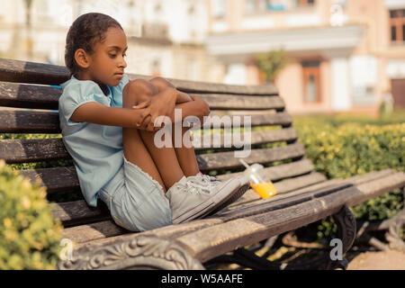 Encantado negativo femenino poco abrazar las rodillas