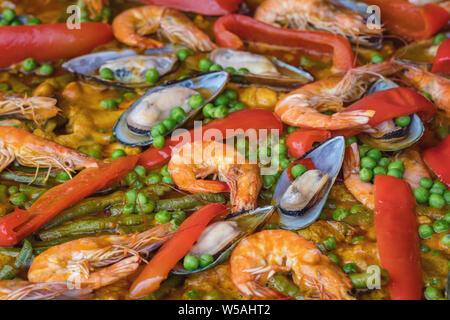 Spanish paella de mariscos en sartén con mejillones, gambas y verduras. Paella de mariscos cerca de fondo Foto de stock