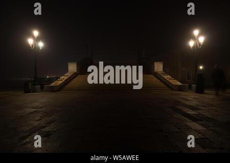 Puente en Venecia por la noche, la sombra de una persona se apresura a través de la escena.