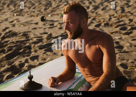 Retrato del hombre que confía con tablas de surf en la playa