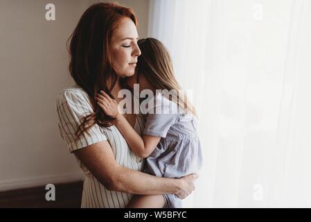 La joven madre caricias con la joven hija mientras cierra los ojos en studio