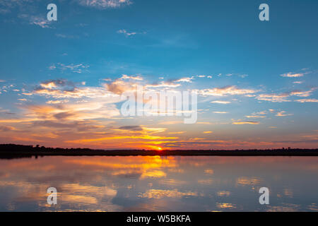 Reflexión Sunset Lagoon. hermosa puesta de sol detrás de las nubes y el cielo azul sobre el paisaje del fondo sobre la laguna. espectacular cielo con nube a sunse