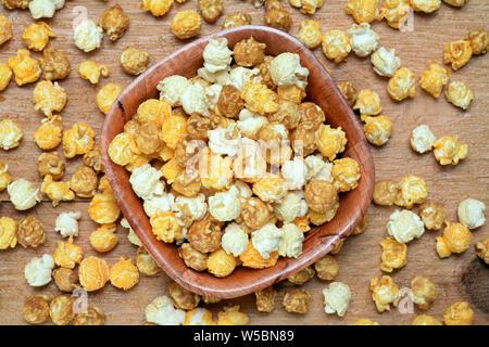 Palomitas de maíz caramelizadas en Wooden bowl en mesa