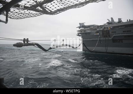190722-N-JG119-1037 OCÉANO PACÍFICO (22 de julio de 2019) el portaaviones USS Theodore Roosevelt (CVN 71) envía una sonda de reabastecimiento a la clase Ticonderoga crucero de misiles guiados USS Bunker Hill (CG 52) durante una reposición en alta mar. Bunker Hill está realizando operaciones rutinarias en el Océano Pacífico Oriental. (Ee.Uu. Navy photo by Mass Communication Specialist Janine 3ª clase F. Jones/liberado) Foto de stock
