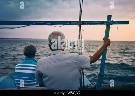 Trabajo duro en el mar. Dos pescadores en barco de pesca al amanecer cerca de la costa de Sri Lanka.