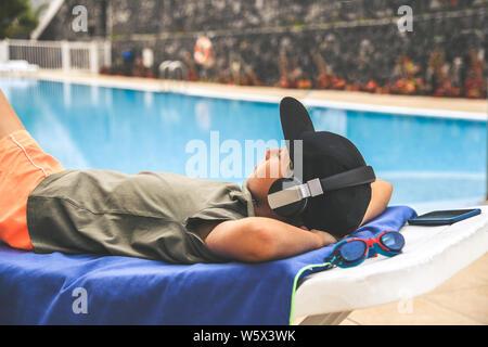 Joven relajante piscina reproduce música con el smartphone de moda escuchar streaming de niño cerca de una piscina en un día soleado de verano Teen disfrutando holida