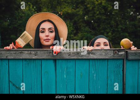 Tom Sawyer Pretty Woman en el sombrero de paja de pie delante de la valla. La mujer una valla de madera pintada. Foto de stock