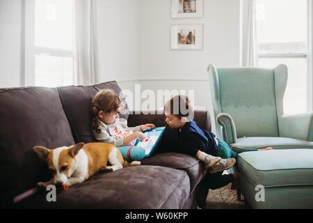 Chico y chica sentada en el sofá con corgi pupply y tablet