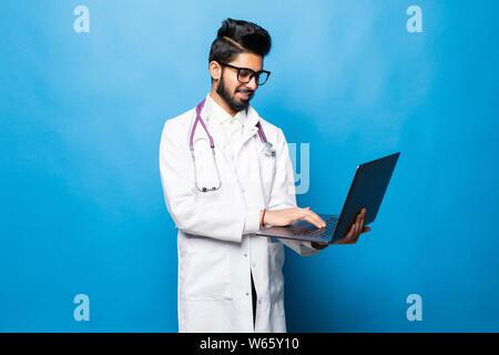 Doctor indio de pie en el estudio mientras se trabaja con el portátil, aislado sobre fondo azul.
