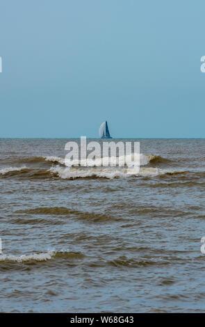 Un velero o yate en el horizonte con las olas en la orilla en primer plano.