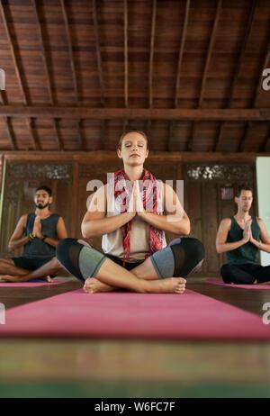 Mujer hermosa meditación profesor dando curso a dos hombres multiétnicas en las esteras del yoga en templo tradicional en Bali Indonesia