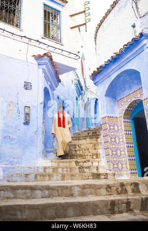 Un viejo hombre marroquí, vestida con el tradicional Djellabah está caminando por el estrecho callejón de Chefchaouen, Marruecos.