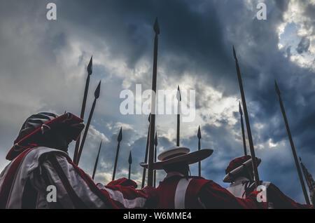 Caballeros medievales guerreros celebración lanza listos para la batalla. Uniformes rojo y blanco. Fotografiado con el espectacular cielo antes de la tormenta. Lucha, concepto del ejército, conceptual. Historia, antecedentes históricos. Foto de stock