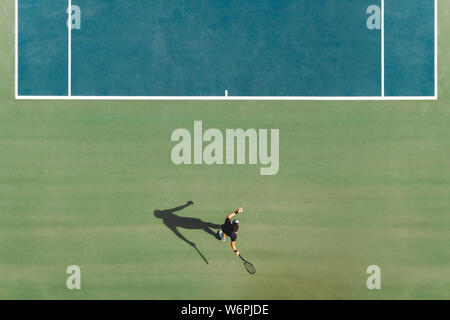Vista aérea del joven jugador de tenis masculino jugando en pista dura. Golpear a un jugador de tenis profesional forehand en corte.