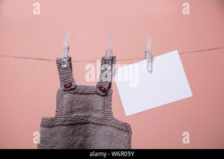 Ropa de bebé tejida y tarjeta virgen colgando de una línea de ropa