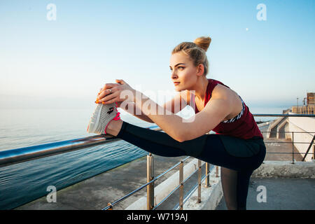 Un atractivo sportswoman estiramientos en la playa, preparando para ejecutar