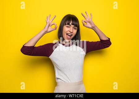Retrato de un joven alegre Pretty Woman mostrando bien gesto aislado posando sobre pared amarilla de fondo.