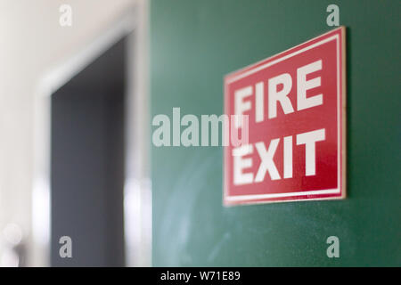Señal de salida de incendios montado en la pared verde del corredor.