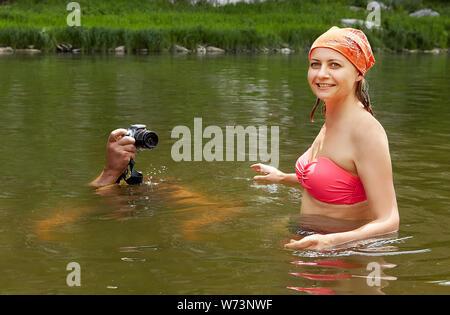 Hermosa joven mujer en bañador mojado está de pie en el río mientras el hombre está tomando fotos con la cámara digital de la superficie del agua, el eco-turismo.