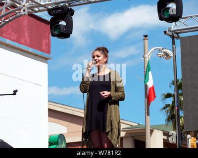 Joven, morena, mujer caucásica en escenario elevado con micrófono contra el cielo azul. Día de San Patricio 2016 Festival de bloque de Corpus Christi, Texas, Estados Unidos.