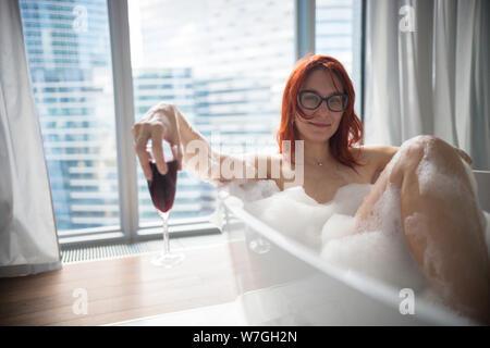 Una mujer sonriente jengibre tumbado en el baño de espuma y sostener un vaso de vino tinto - una vista en un moderno edificio de vidrio de las ventanas panorámicas