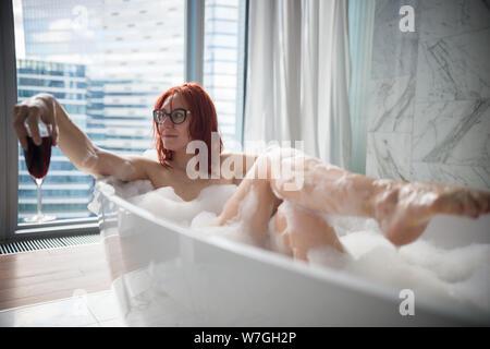 Una mujer de jengibre tumbado en el baño de espuma y mirando hacia el lado - sosteniendo un vaso de vino tinto - una vista en un moderno edificio de cristal de la panorámica