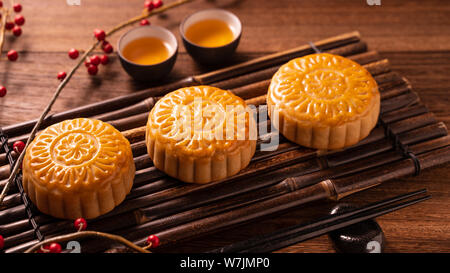 Chino tradicional pastelería Mooncake Moon Cake con tazas de té de bambú bandeja servingwarning sobre fondo de madera Mid-Autumn Festival, cerca.