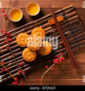 Chino tradicional pastelería Mooncake Moon Cake con tazas de té de bambú bandeja de servir de fondo para madera Mid-Autumn Festival, vista superior, plano laical.