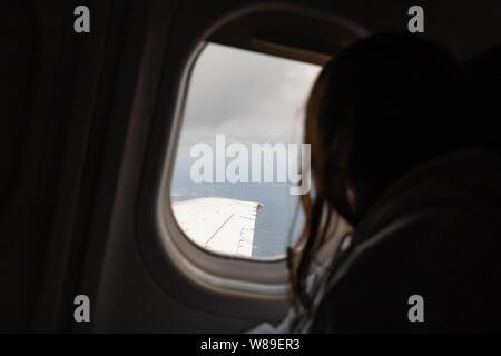 Chica mirando por la ventana del avión en vuelo mientras viaja