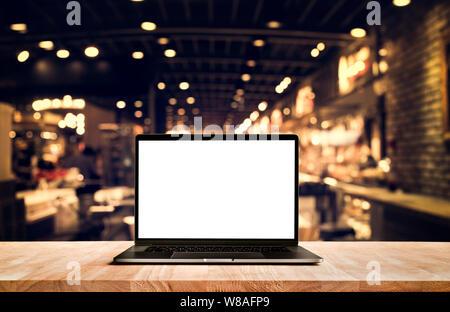 Equipo moderno,portátil con pantalla en blanco en el cuadro cafetería fondos Foto de stock