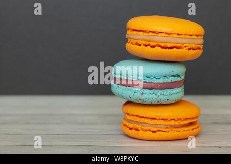 Macarons naranja y azul sobre un fondo oscuro, las galletitas francesas como un regalo para las vacaciones Foto de stock