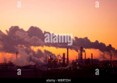 Paisaje industrial borrosa. Violeta de los tubos de humo al atardecer en las afueras de la ciudad. Los problemas ambientales y la contaminación del aire.