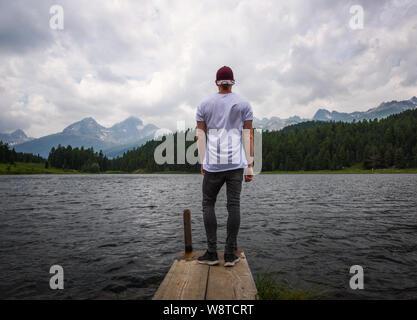 Los jovenes turistas con vistas al precioso lago alpino de Staz en Suiza