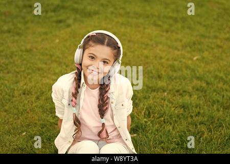 Chica con auriculares de fondo de la naturaleza. La influencia positiva de la música. Niño Niña disfrutando de la música moderna de auriculares. Infancia y adolescencia el gusto musical. Niña escuchando música disfrutar de sus canciones favoritas.