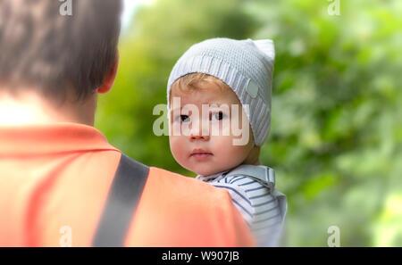 El niño en los brazos de papá. Retrato de un niño niña un muchacho en un sombrero mira sobre el hombro mientras está sentado en los brazos de su padre. Hermoso pequeño ba