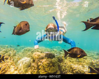 Mujer feliz en el esnórquel Máscara submarina de buceo con peces tropicales de arrecifes de coral mar piscina. Estilo de vida viajes de aventura al aire libre, deportes acuáticos, natación