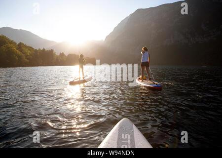 Madre e hijo remando en sup en el manantial de aguas color esmeralda del lago alpino de Bohinj, Eslovenia al atardecer