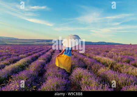 Chica en un campo lila al atardecer. Soleada tarde de verano en Crimea. El concepto de la felicidad y la libertad.