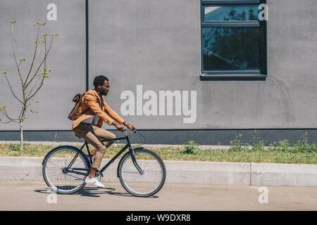 Elegante empresario afroamericano montando bicicleta en calle soleada,