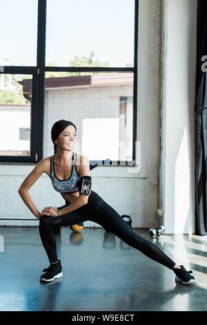 Mujer alegre en ropa deportiva haciendo ejercicio en el gimnasio sentadilla