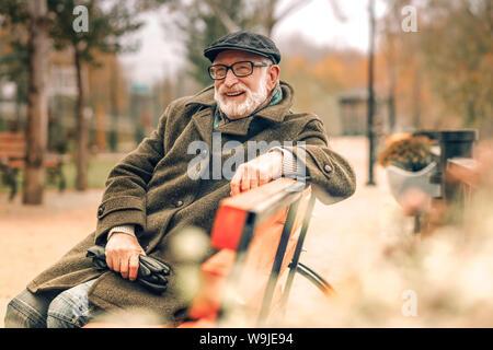 Senior elegante hombre sentado en un banco en el parque Foto de stock